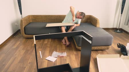 vidalar : A young man independently collects furniture in the living room of his house. A man collects a computer desk.