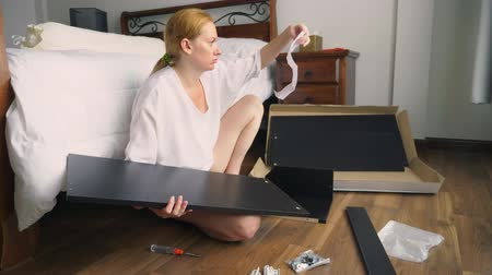 old maid : Assembling furniture at home, a housewife assembles a computer desk using hand tools. Stock Footage