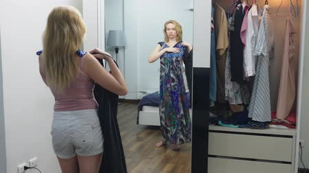 решить : Clothing, wardrobe, fashion, style and concept of people. puzzled blonde makes a choice of clothes, standing near the closet and looking at herself in the mirror