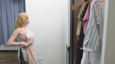 megpróbál : Clothing, wardrobe, fashion, style and concept of people. puzzled blonde makes a choice of clothes, standing near the closet and looking at herself in the mirror