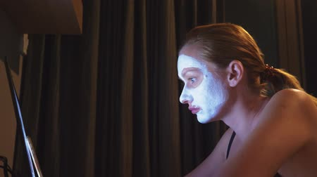 hydratační : young woman with cosmetic mask on face working with laptop at home in the evening. naturalness