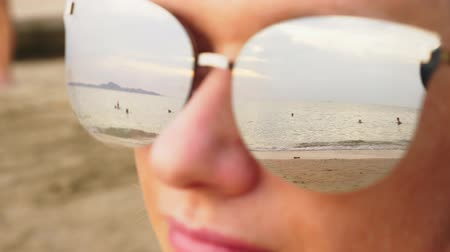 ultraviolet : Close-up face of a happy woman in sunglasses. The beach with the resting people is reflected in the glasses.