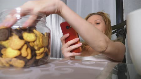 coisas : hungry sad woman sits in a living room at a table at night, she eats a liver and uses her smartphone