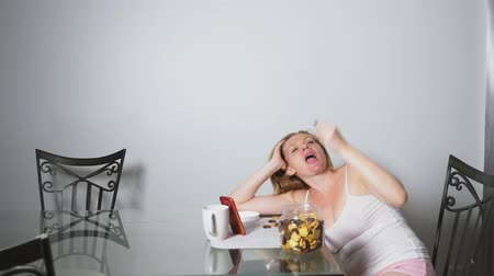 бдительность : hungry sad woman sits in a living room at a table at night, she eats a liver and uses her smartphone