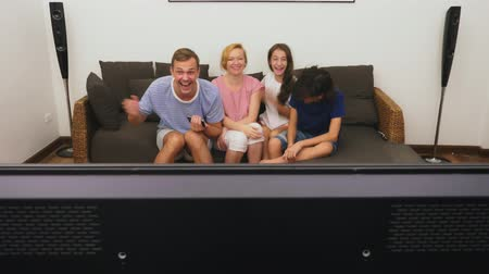 nevető : Charming family, mom, dad, daughter and son are watching TV in the living room together Stock mozgókép