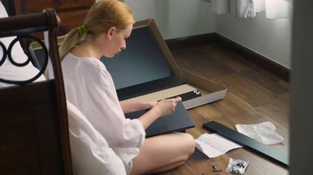 feminism : Assembling furniture at home, a housewife assembles a computer desk using hand tools. Stock Footage
