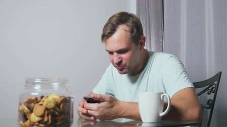 ostražitost : hungry sad man sits in a living room at a table at night, he eats a liver and uses her smartphone