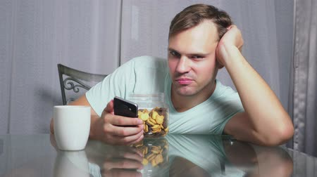 бдительность : hungry sad man sits in a living room at a table at night, he eats a liver and uses her smartphone