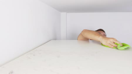 keeper : home cleaning concept. a man wipes dust from a high cabinet in his house