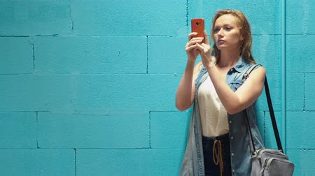 denim : Attractive blonde girl uses red smartphone against a blue wall