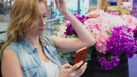 magnólia növény : A beautiful young woman is sitting on a bench in a large modern shopping center near a flower bed. she uses her smartphone