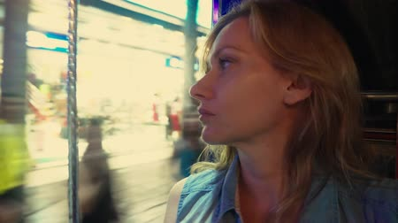 rickshaw : Beautiful tired young woman blonde portrait inside a tuk tuk on a night street. tourism concept