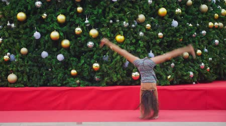 jimnastik : happy girl doing gymnastic somersault on the background of the Christmas tree and palm trees in a tropical city. The concept of New Years travel to warm countries.