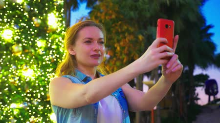 telefon : happy woman on the background of the Christmas tree and palm trees in a tropical city. The concept of New Years travel to warm countries. using the phone Wideo