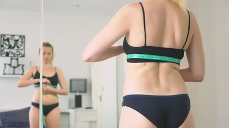 centímetro : The concept of overweight and weight loss. A woman measures herself with a measuring tape in the bedroom. Looking at herself in the mirror