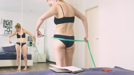 centímetro : The concept of overweight and weight loss. A woman measures herself with a measuring tape in the bedroom, Looking at herself in the mirror, and writes the results into a notebook