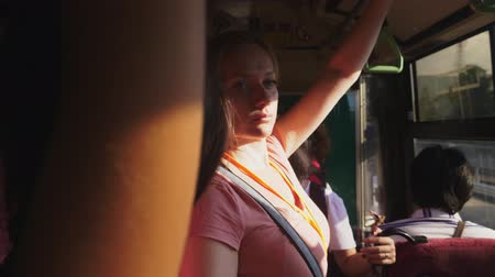holding onto : A tired woman rides on a bus while standing and holding onto a rail