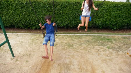 rodzeństwo : boy and girl teenager swinging on a swing with bare feet on the green lawn of the backyard of his house