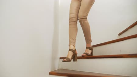 legs only : close-up, female legs in beige tight fitting pants and heeled sandals walking along a wooden modern staircase Stock Footage