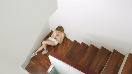 correspondência : girl in shorts sits on the stairs at home and uses a smartphone