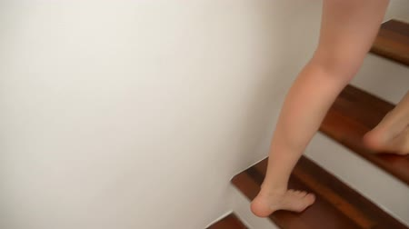 legs only : Close-up. The bare feet of a Caucasian woman climb to the top of the wooden stairs. Stock Footage