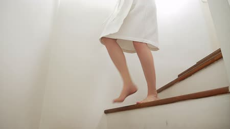 stepping : Close-up. female legs rises to the top of a wooden ladder. woman in a dressing gown walks up the steps