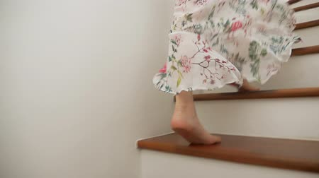escada : Close-up. Female bare feet descend the wooden stairs. a woman in a beautiful long skirt walks down the stairs.