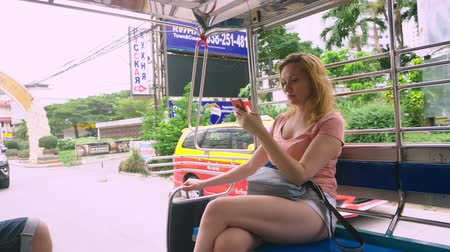 risciò : Thailand, Pattaya, Jomtien Beach, 07. 12. 2018. A beautiful young woman rides in a tuk-tuk in the afternoon and uses a smartphone. tourism concept