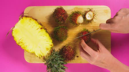 ananás : top view, female hand cuts fruits with a knife on a wooden board, pineapple and rambutan. The concept of natural healthy food.