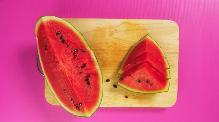 meyva : top view, female hand cuts fruit with a knife on a wooden board, red watermelon. The concept of natural healthy food. Stok Video