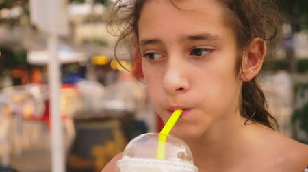tiredness : tired of the heat the girl drinks a cold cocktail through a straw, close-up Stock Footage