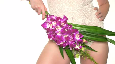 orquídeas : Woman holding a flower on the background of underwear, the concept of female health and body care