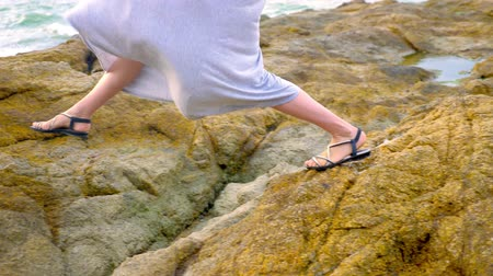 scatters : close-up. womens legs in sandals and a long gray skirt are on the rocky seashore at low tide.