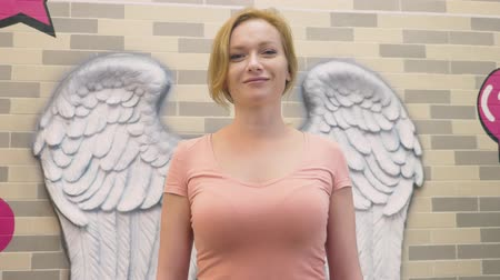 bas : A blond woman stands on the background of a wall with bas-reliefs in the form of angel wings. Dostupné videozáznamy