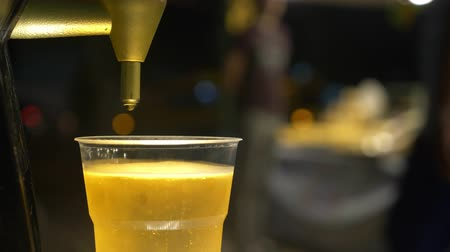 clear liquid : close-up. Men hands pouring beer into a plastic cup. street food. Stock Footage