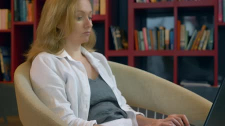 hotel suite : Young woman smiling. uses a laptop while sitting in a modern library. Stock Footage