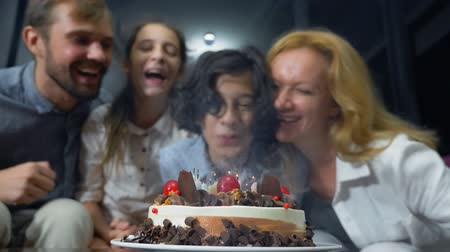 kinderwens : Happy smiling boy blowing candles on her birthday cake. children surrounded by their family. birthday cake with candles Stockvideo