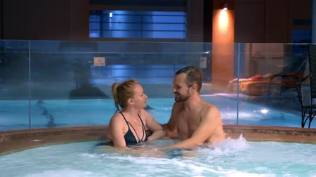 джакузи : Couple relaxes in an outdoor hot tub. Happy young woman and man relaxing in hot water near the pool.