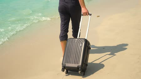 voyager : A young man in pants and a classic shirt with a suitcase walks along the beach against the backdrop of the turquoise sea. freelance concept, rest