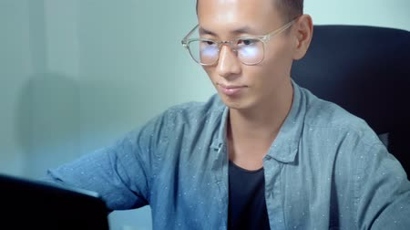 Young handsome asian man using his laptop, sitting at desk in office
