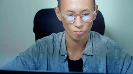 домашнее задание : Young handsome asian man using his laptop, sitting at desk in office