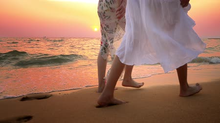pegada : close up . bare feet on the beach. two young women in white dress walking on the beach at sunset