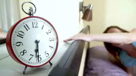 alerta : Red alarm clock close-up, on a blurred background, the girl is angry that the alarm clock has rung Stock Footage