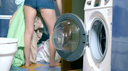 linen : concept of washing at home. woman puts laundry in the washing machine
