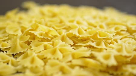 makarna : raw pasta. Farfalle closeup on wooden table Stok Video