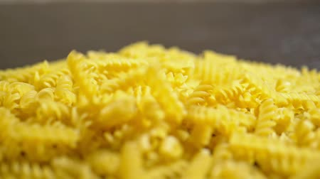 равиоли : raw pasta. Fusilli, closeup fall on a wooden table,