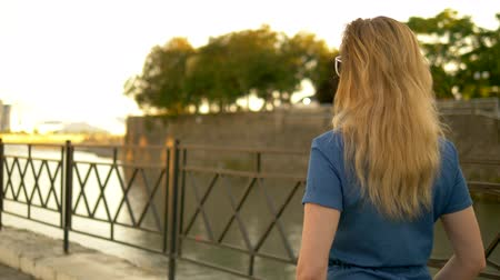 go away : back view. medium plan. beautiful young woman blonde in denim overalls walks through the summer city park