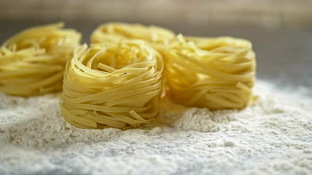 cooking salt : Fettuccine, raw pasta, closeup lie in white flour on a wooden table Stock Footage