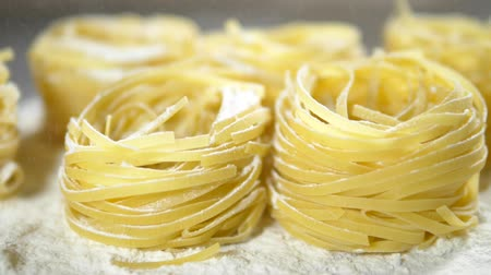 makaróni : Fettuccine, raw pasta, closeup lie in white flour on a wooden table Stock mozgókép