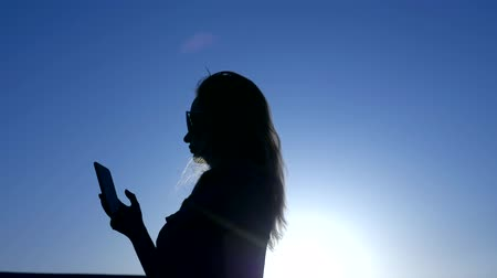 iluminado para trás : Silhouette of a woman with a smartphone with flying hair on a background of blue sky sunset